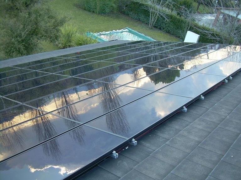 dei pannelli solari e con vista di un prato e una piscina