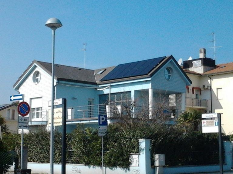 una villetta vista da lontano con un impianto fotovoltaico installato sul tetto
