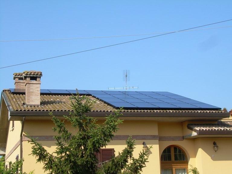 impianto fotovoltaico installato sul tetto di una villetta gialla