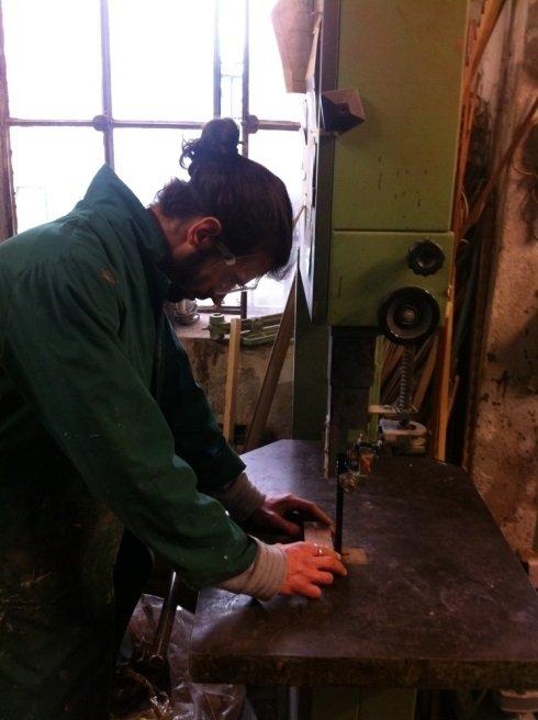 un ragazzo durante un lavoro di restauro su un banco in legno