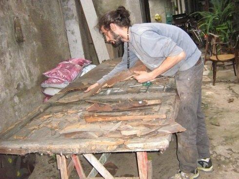 un ragazzo al lavoro su una porta da restaurare