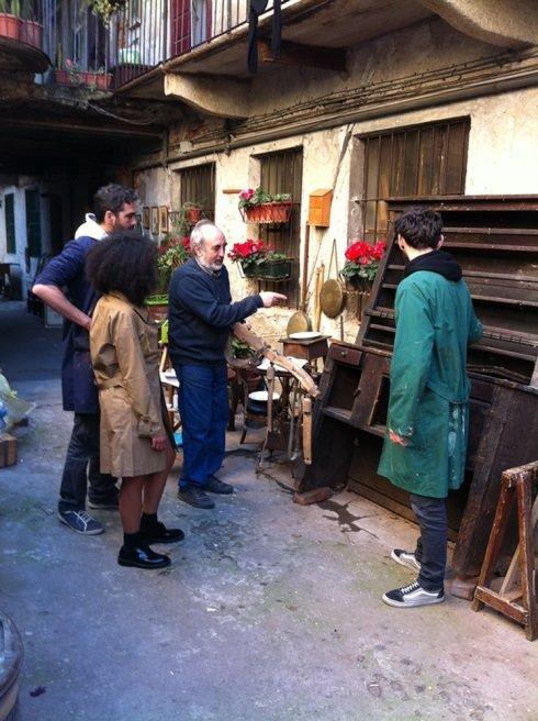 un signore che indica dei mobili in legno e delle persone accanto