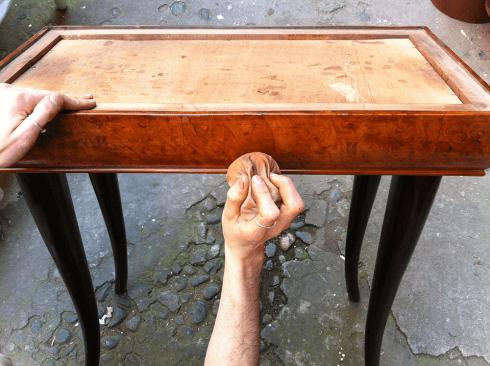 una mano con una spugnetta che lucida un cassetto in legno