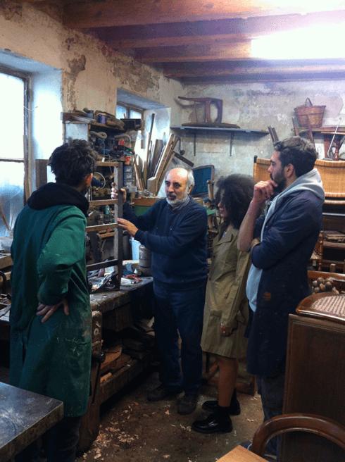 un signore che parla con dei ragazzi in un laboratorio di restauro