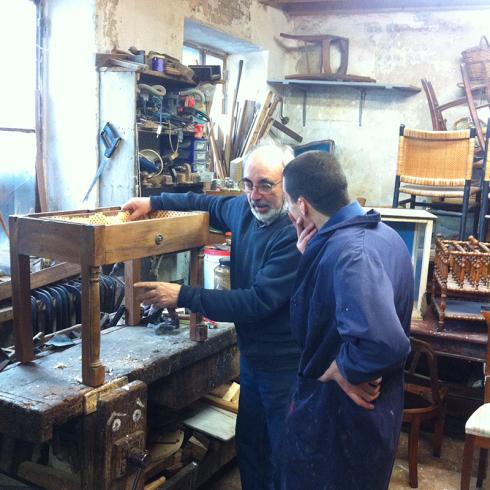 un signore che indica un tavolino in legno e un ragazzo accanto