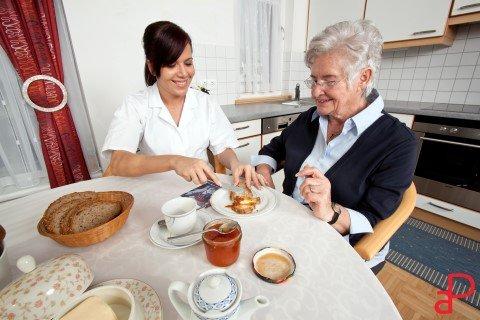 assistente sorridente aiuta una signora anziana a fare colazione spalmando la marmellata sulle fette biscottate