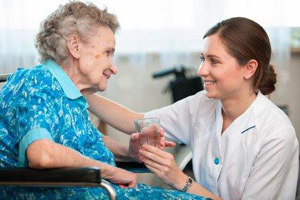 badante porge un bicchiere d'acqua ad anziana