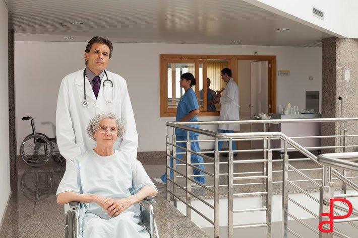 dottore spinge anziana su carrozzina in ospedale