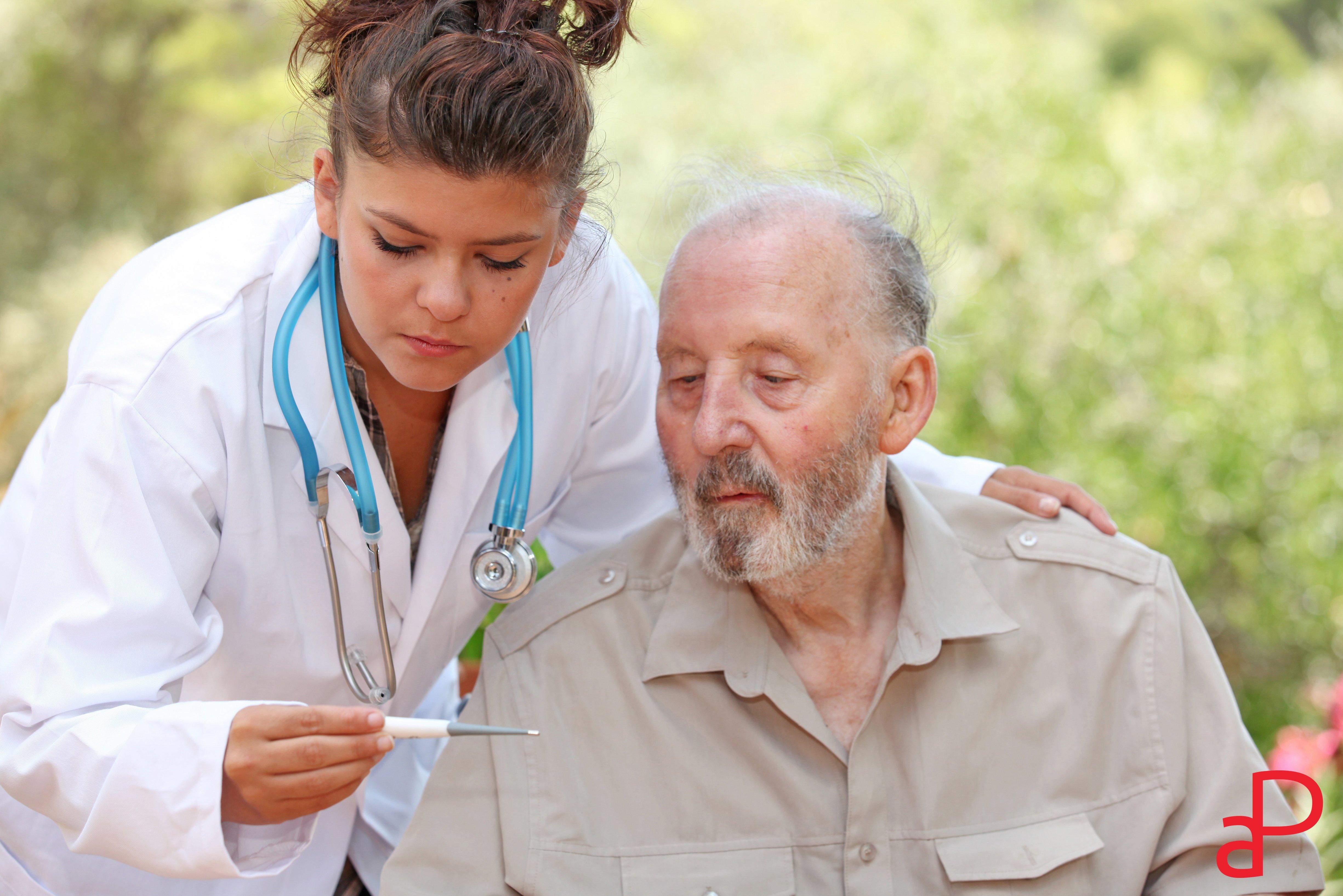 infermiera misura la temperatura ad anziano