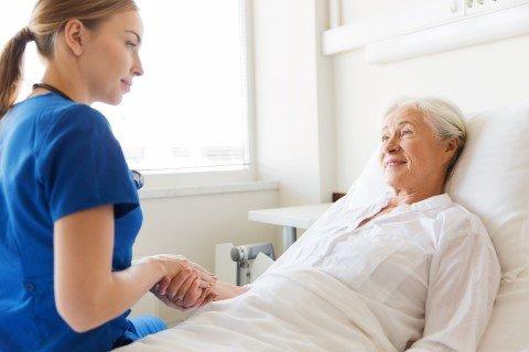 anziana in un letto con infermiera vicina