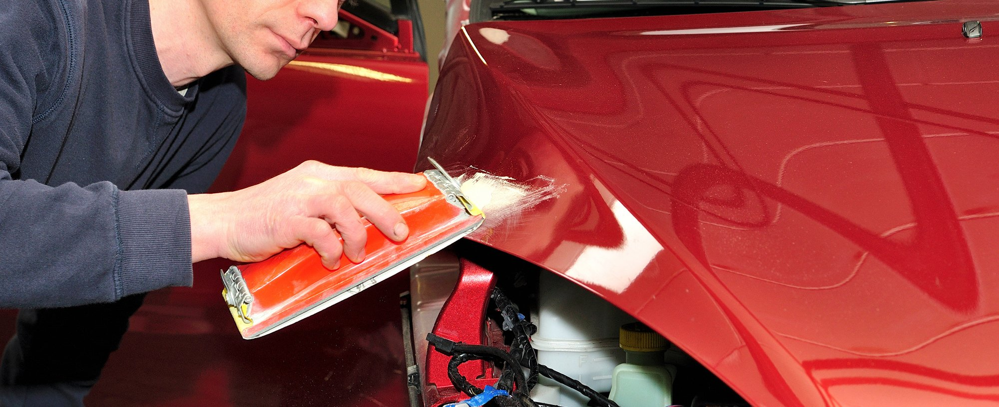 auto body technician sanding damaged quarter panel