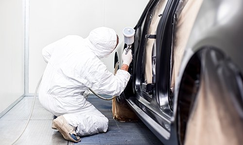 Car repair experts working on a dent removal job