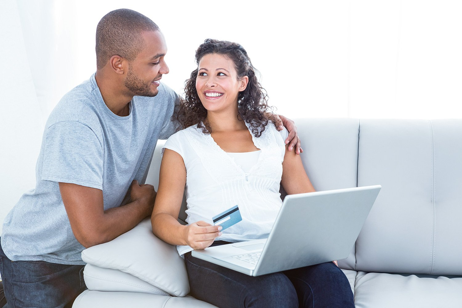 Happy couple shopping online sitting on sofa at home
