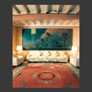 Salotto dalle linee pulite con quadro e tappeto antichi