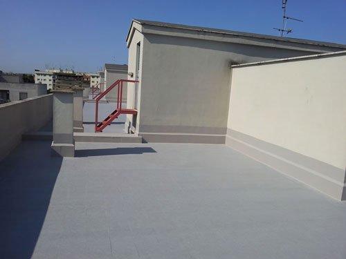 un terrazzo con pavimentazione dipinta di grigio e impermeabilizzata