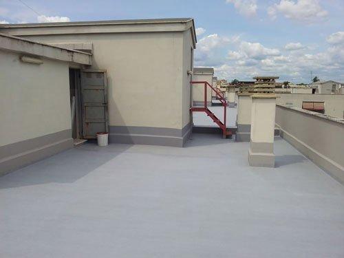 un terrazzo con pavimentazione dipinta di grigio chiaro e impermeabilizzata