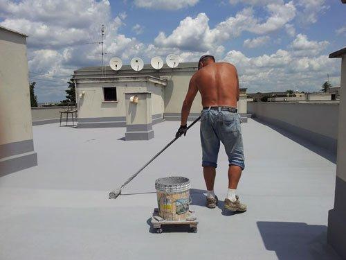 un uomo con un rullo che dipinge la pavimentazione di  un terrazzo