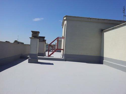 un terrazzo con pavimentazione dipinta di grigio chiaro, impermeabilizzata con vista di una scaletta rossa