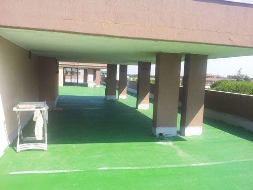 un porticato sul tetto e la pavimentazione dipinta di verde