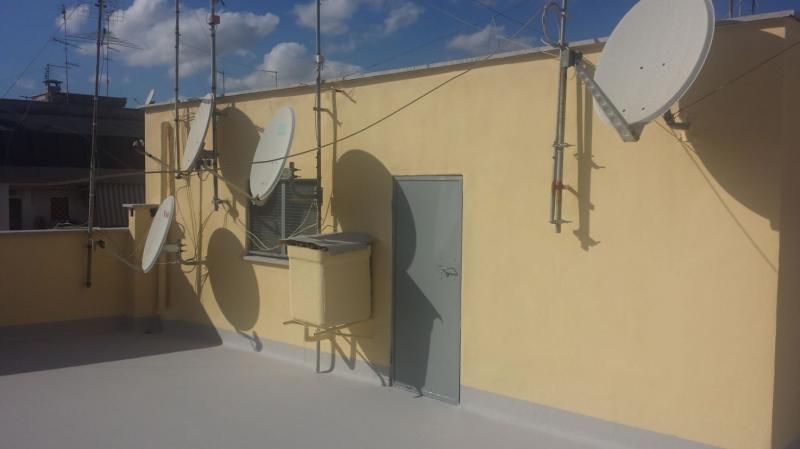 il muro giallo con la porta grigia di accesso al terrazzo sul tetto con vista delle parabole