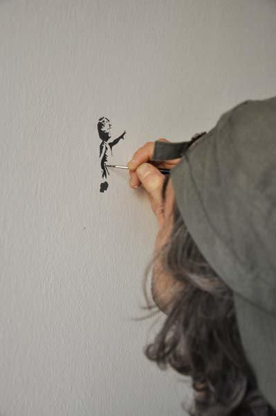 pittore riproduce la bambina con il palloncino di Bansky