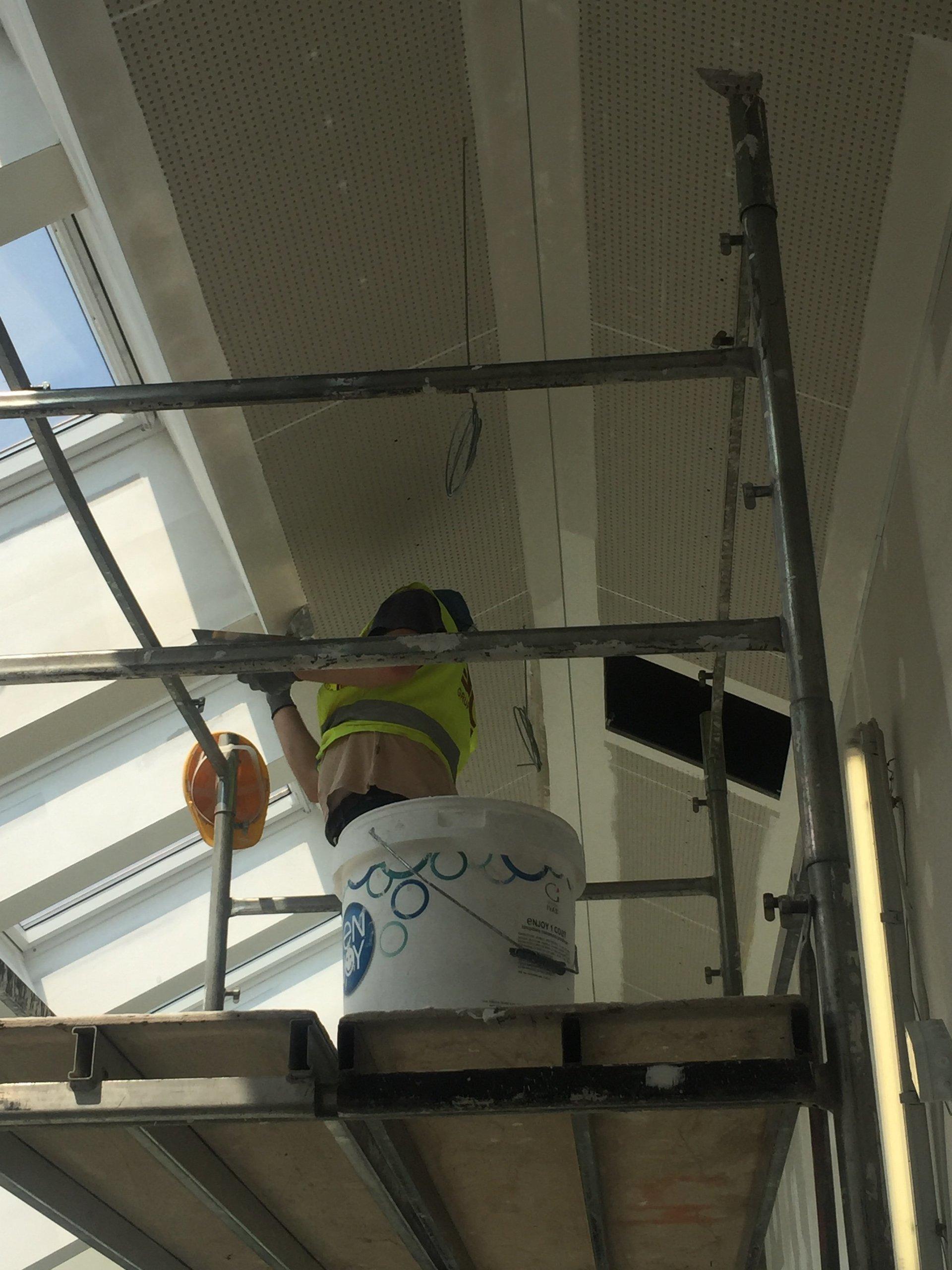 muratore lavora un soffitto