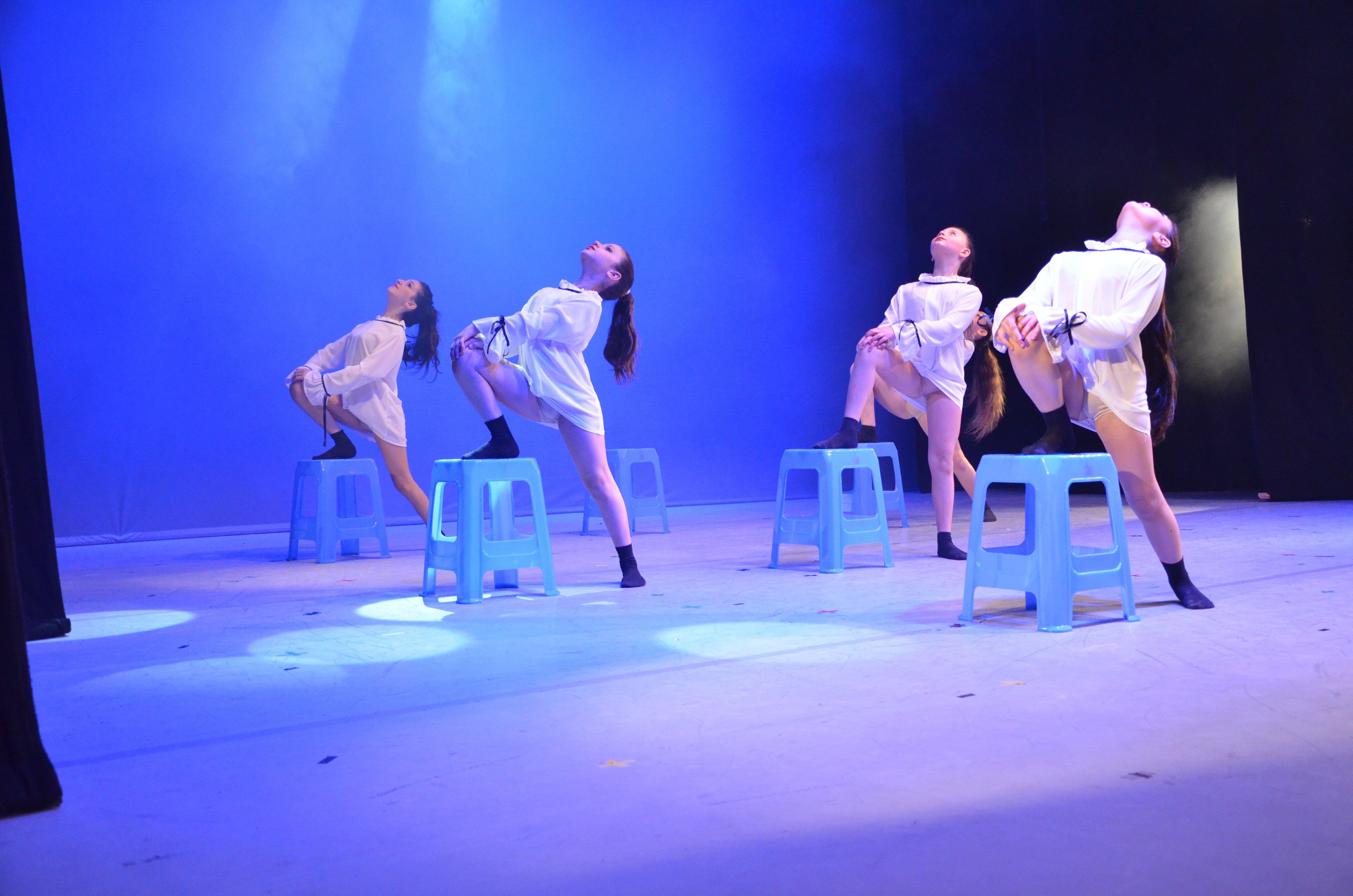 quattro ragazze che ballano con una gamba sulla sedia
