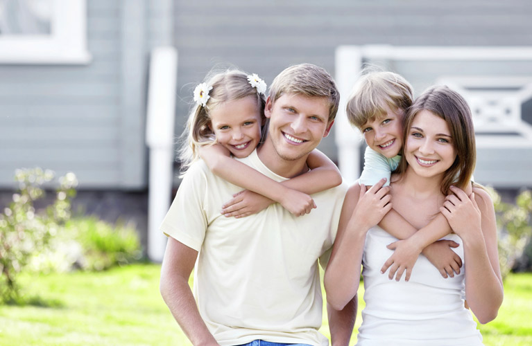 family of four outside there home