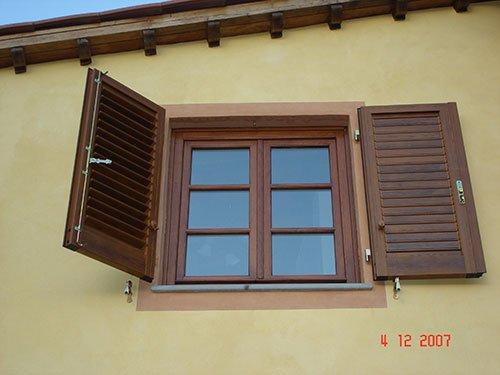 delle finestre con delle persiane in legno