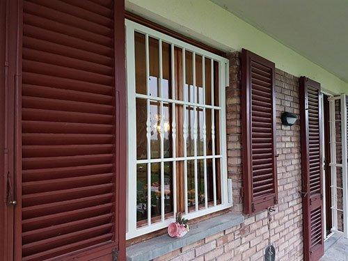 una finestra con delle griglie e delle persiane aperte