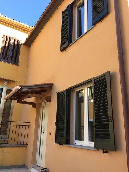 la facciata di un condominio con delle persiane e le finestre