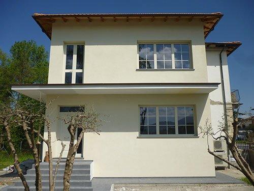 una casa bianca a 2 piani con vista delle finestre