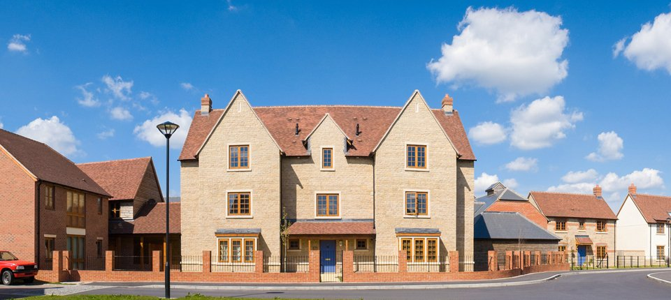 A large building of honey coloured brick with cobalt blue front door and timber window frames
