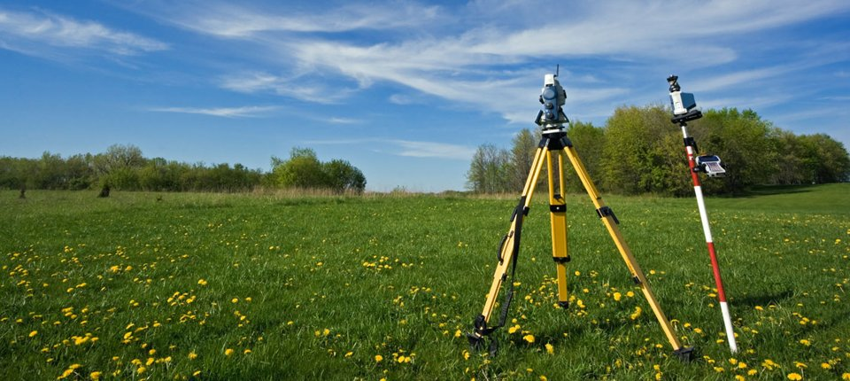 Surveying equipment in the middle of a field dotted with buttercups and surrounded by trees