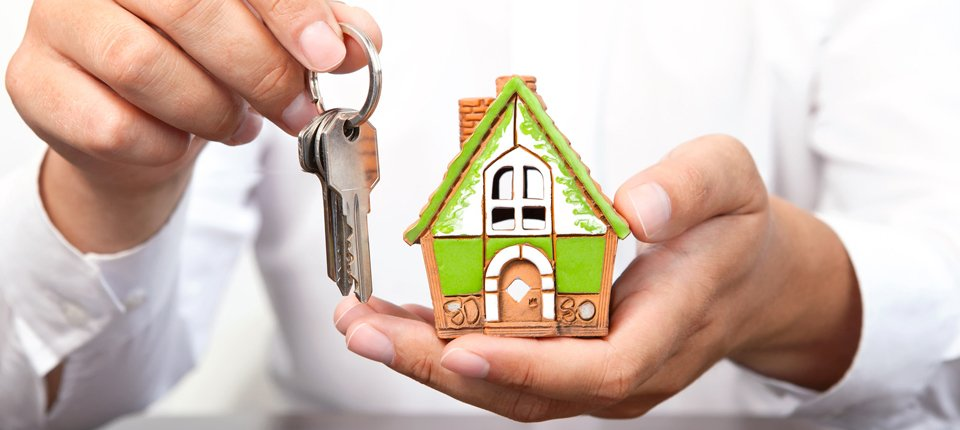 A man's hands holding a model of a house in terracotta, green and white, and a bunch of keys