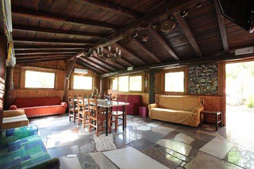 sala ricreativa con soffitto in legno, ampi balconi, divani colorati , tavolo con sedie