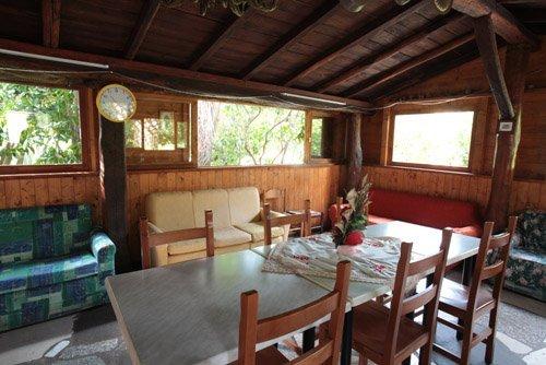 tavolo con cinque sedie, divani, tre finestroni, pareti in legno