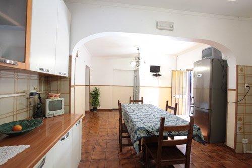 cucina in legno chiaro, tavolo con sedie, frigo