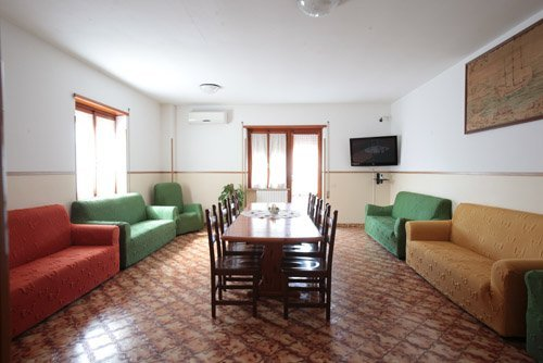 sala con divani colorato ed al centro tavolo con sedie