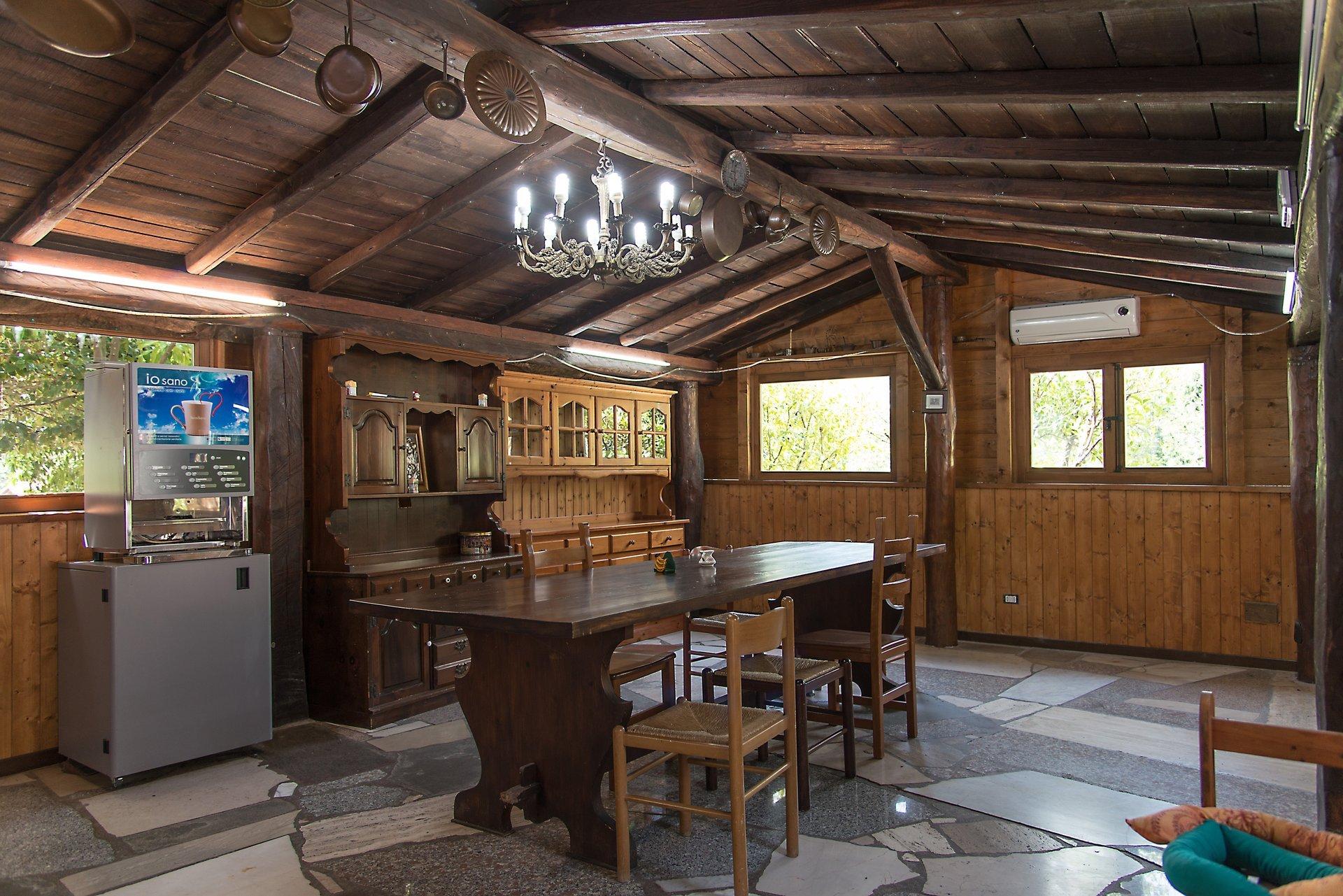 sala interna in legno con credenze e tavolo con sedie