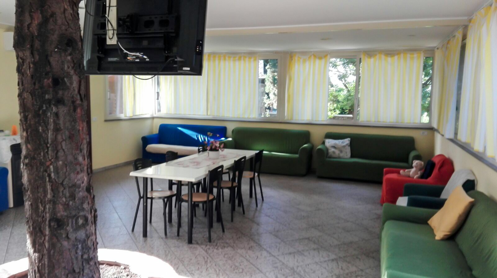 tv, tavolo con sedie e divani blu