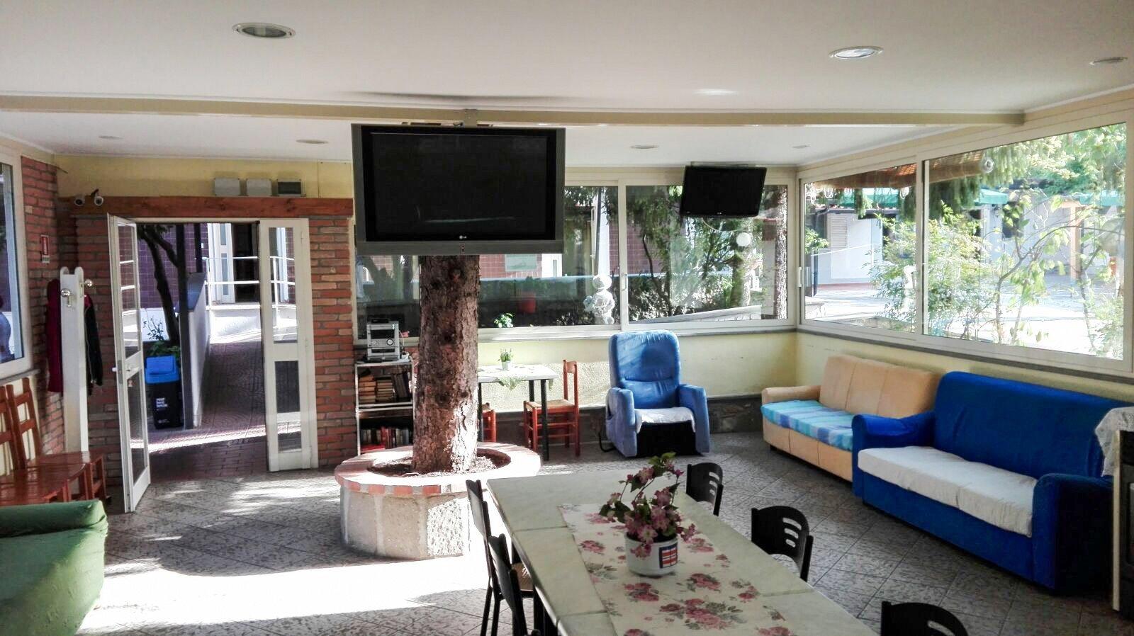 sala ricreativa con tavolo e sedie, poltrona blu e tv