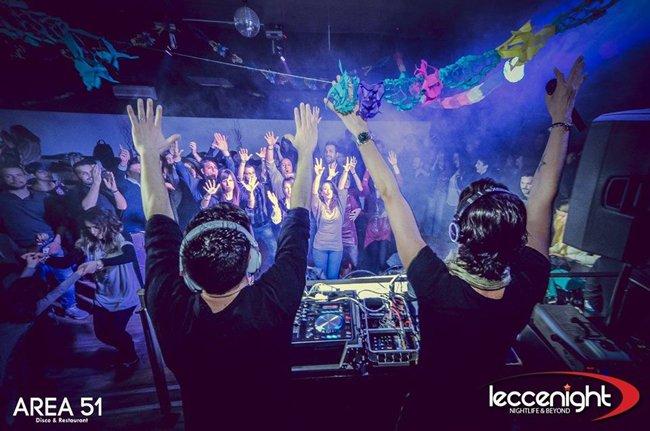 due DJ con le mani in aria di fronte alla pista da ballo