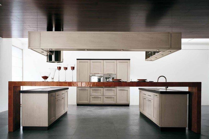 una cucina moderna con mobili in legno bianco una cappa appesa al soffitto e un grande tavolo di legno