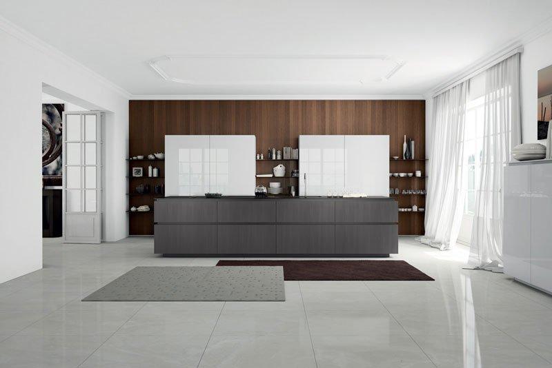 un'ampia cucina con una pensola grigia scura e due armadi bianchi davanti a un muro in legno