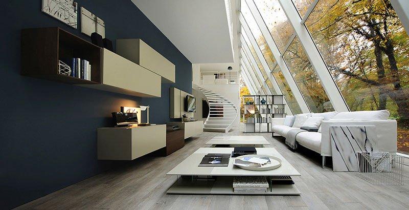 un'ampia sala di un appartamento moderno con un divano bianco, un tavolino, dei mobili a muro e in fondo vista delle scale