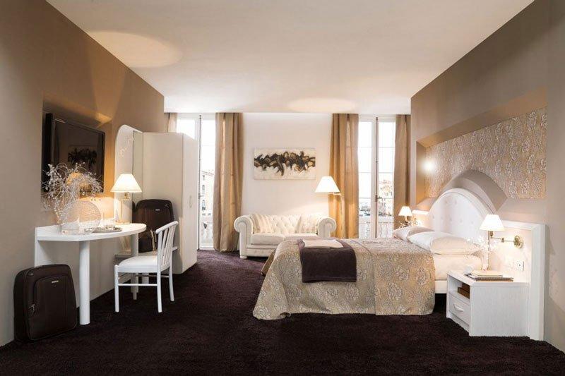 una camera con sulla sinistra una scrivania bianca con una lampada, sulla destra un letto e in fondo un divano bianco