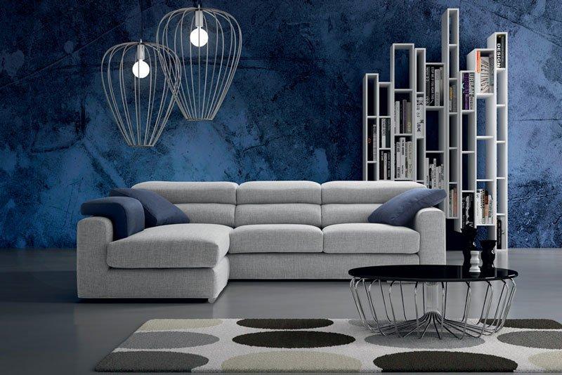 un divano angolare grigio in una sala con muri blu
