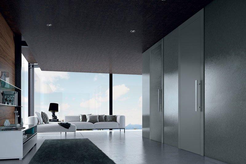 un salotto moderno con dei divani bianchi, sulla sinistra un mobile e sulla destra vista di due porte