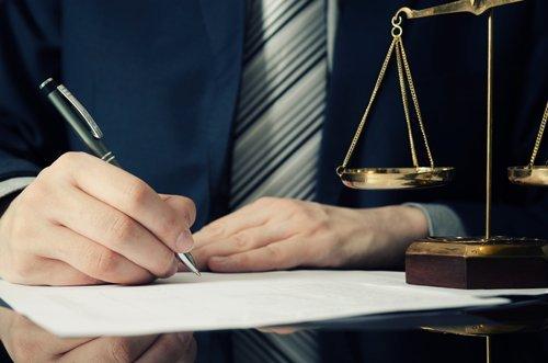un avvocato mentre scrive accanto alla bilancia della giustizia